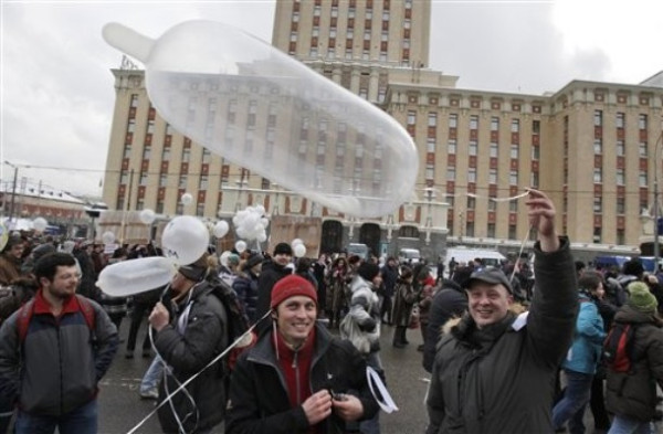 Protesters carry an inflated condom in a reference to Prime Minister Vladimir Putin's sardonic comparison of protesters' white ribbons worn as emblems to condoms, as they gather to protest against alleged vote rigging in Russia's parliamentary elections on Sakharov avenue in Moscow,  Russia, Saturday, Dec. 24, 2011. Tens of thousands of demonstrators on Saturday cheered opposition leaders and jeered the Kremlin in the largest protest in the Russian capital so far against election fraud, signaling growing outrage over Prime Minister Vladimir Putin's 12-year rule. (AP Photo/Ivan Sekretarev)